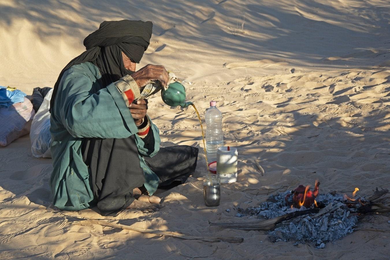 Un classico individuo delle tribù berbere del deserto che degusta lo speciale tè algerino