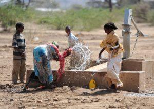 Donne e bambini raccolgono acqua potabile