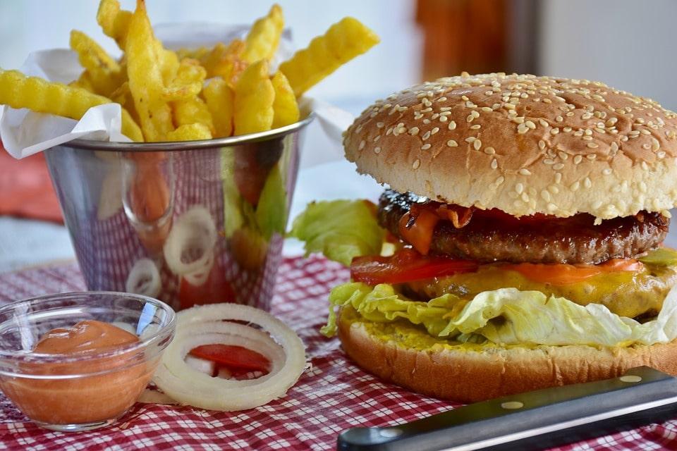 Tipico pranzo da fast food con Hamburger, patatine e salse varie
