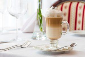 submarino latte con sciroppo al cioccolato con sopra panna spry servito in un bicchiere di vetro su piattino