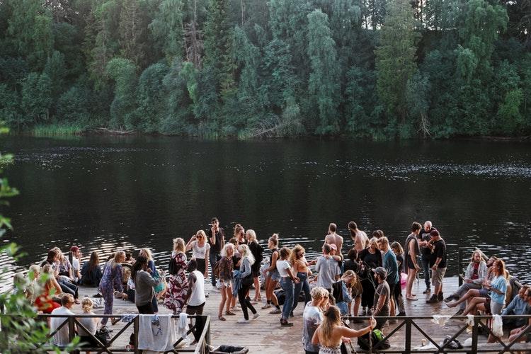 Gruppo di giovani in Australia si riuniscono sulle spiaggie per festeggiare insieme le feste mangiando e bevendo con musica e balli